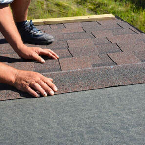 man's hands laying shingles
